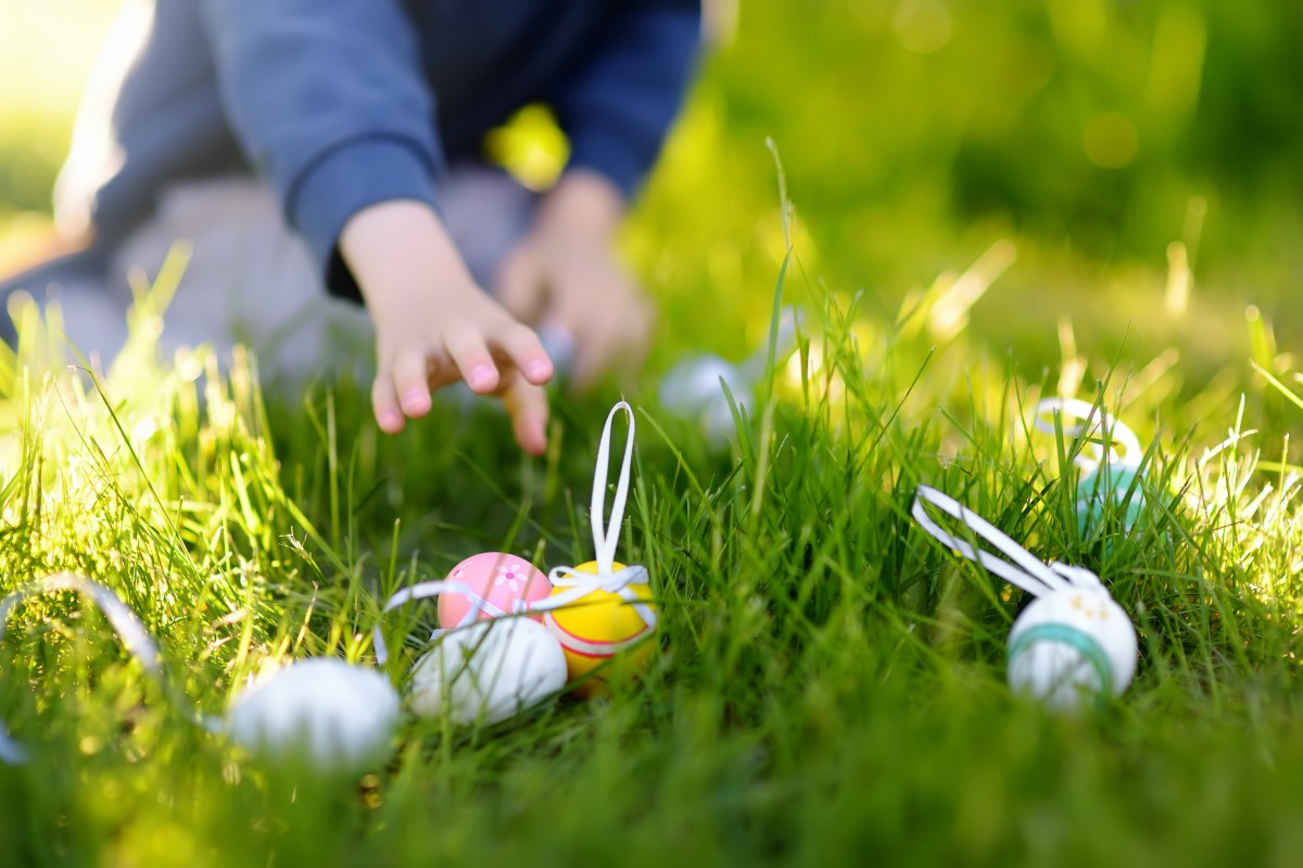 child reaching for Easter egg in grass